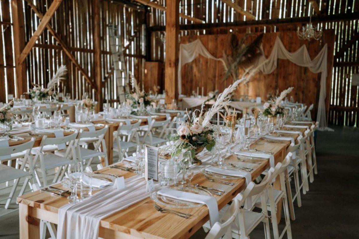 dekoracja stodoły na wesele w stylu boho, z elementami dekoracji w kolorze beżowym i różowym